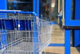 Blauer Einkaufswagen vor Ladentür - 163191299