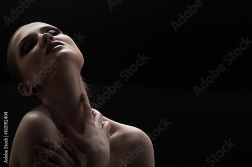 Black and white shot of woman posing sensually holding head up on black background