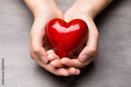 Red wood heart in child hands.
