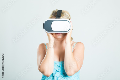 Poster Blonde beautiful pregnant girl wearing 3d virtual reality goggles isolated on background