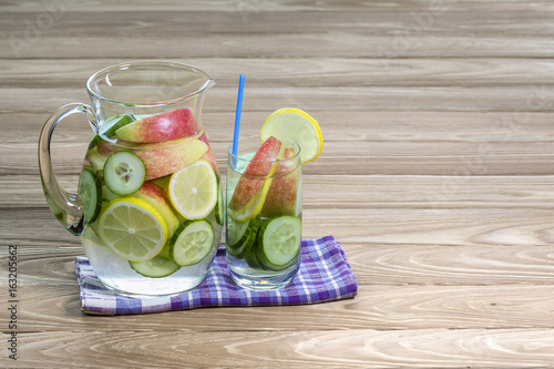 Jug and glass of water with lemon and apple to detoxify