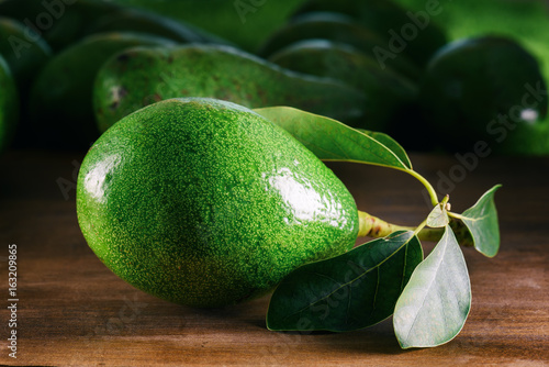 Closeup view of fresh ripe avocado with green leaves