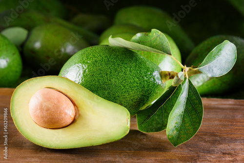 Fresh ripe avocado with green leaves on wooden table