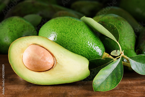 Ripe green avocados with leaves on wooden table