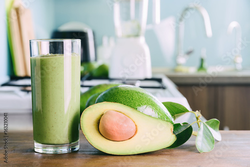Avocado smoothie and ripe avocados on kitchen table