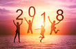 Happy new year card 2018. Silhouette of children girl is jumping on tropical beach with fantastic sunset sky background. Kids holding the number 2018 with sea and sunrise background.