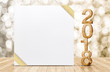 Happy new year 2018 with blank white greeting card with gold ribbon in perspective room at sparkling bokeh wall and wooden plank floor,leave space for display of design