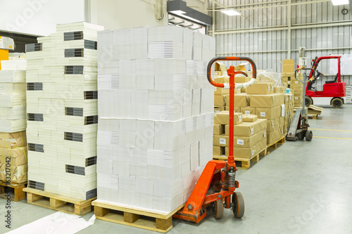 Interior of a warehouse with manual forklift pallet stacker truck equipment, boxes.