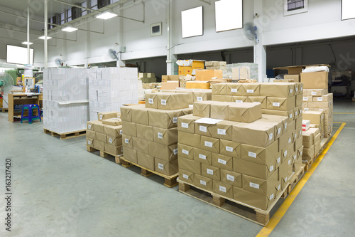 Interior of a warehouse with pallet stacker, boxes.