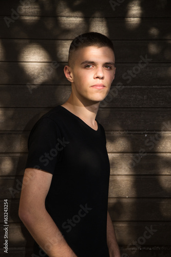 Teenage Boy looking at camera on background of Urban wall