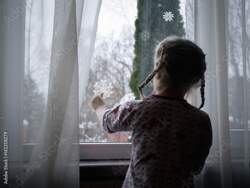 Little girl decorates the window. Paste paper snowflakes. Child is waiting for the New year holiday
