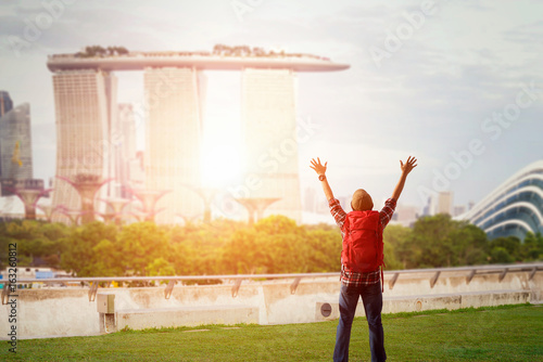 Young man traveler with sky blue backpack and hat holding the map with singapore city downtown background Poster