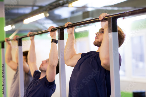 group of young men doing pull-ups in gym