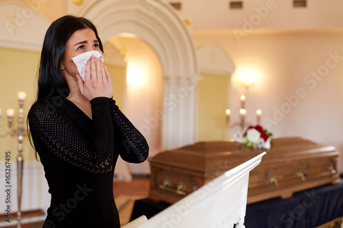 woman with coffin crying at funeral in church
