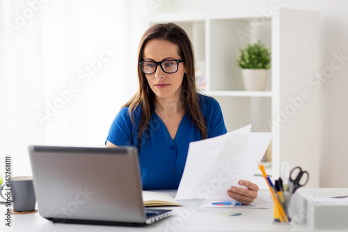 happy woman with laptop working at home or office