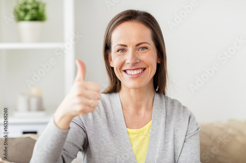 happy smiling woman showing thumbs up at home