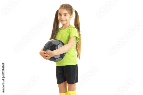 cute little girl in green t-shirt stands in the Studio and holds the ball