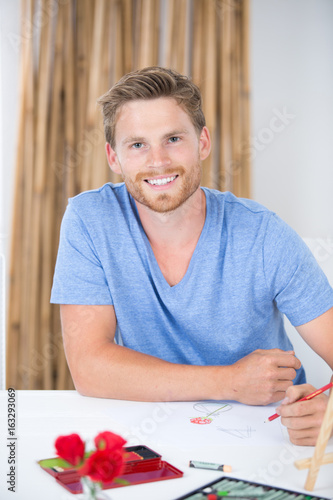 Portrait of young man drawing still life
