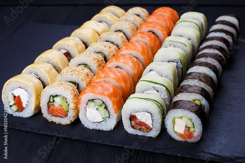 Papiers peints Sushi bar Colorful delicious set of sushi served on black slate, close up. Japanese cuisine, restaurant menu photo.