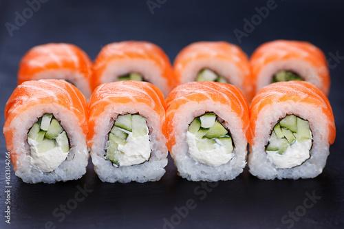 Tasty and fresh philadelphia sushi rolls served on black slate, close up. Delicious Japanese seafood