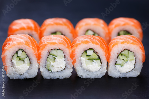 Tasty and fresh philadelphia sushi rolls served on black slate, close up Poster