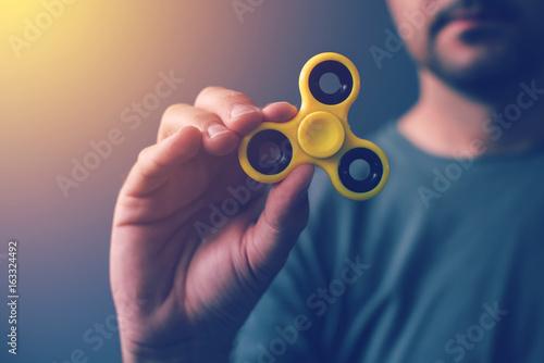 Yellow fidget spinner in male hand