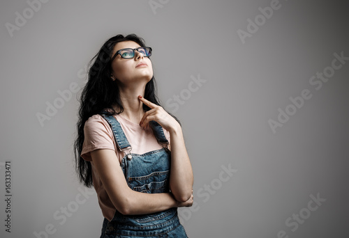 Portrait of smart beautiful brunette girl in eyeglasses with natural make-up, on grey background.