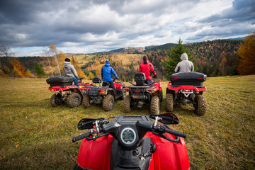 View from quad bike. Four men at ATV enjoying beautiful landscape of rolling countryside and colorful forest under the sky with cumulus clouds in autumn