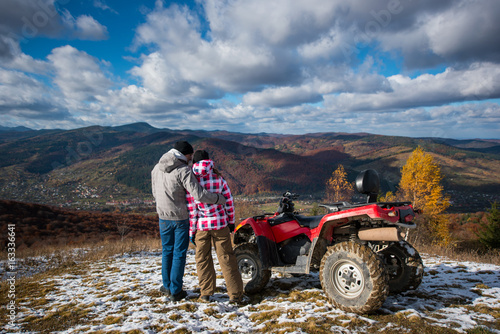 Rear view of a guy hugging a girl near the ATV on a mountain top under the blue sky with cumulus clouds at background of mighty mountains and village in the valley