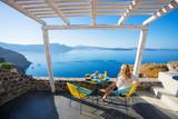 Woman enjoying breakfast with beautiful view over Santorini - 163337459