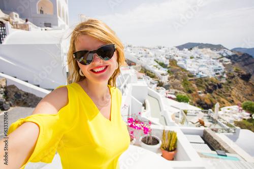 Tourist girl taking selfie in beautiful Santorini island.