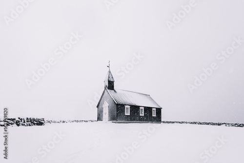 Beautiful minimalistic view of Budir black church in the Snaefellsnes peninsula during severe snowstorm - 163359820