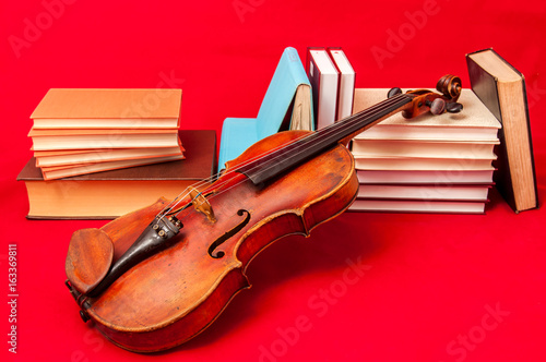 Music instrument old violin on a book and pile of books - 163369811