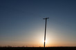 Silhouetted Power Pole On Canadian Prairie At Sunrise