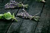 Lavender flowers, rosemary, mint, thyme, melissa with old scissors on a black wooden table. Burnt wood. Spa and cosmetic or cooking background. - 163378675