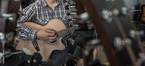 Young man playing the guitar in a shop