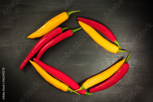Red and yellow chili peppers forming frame on black
