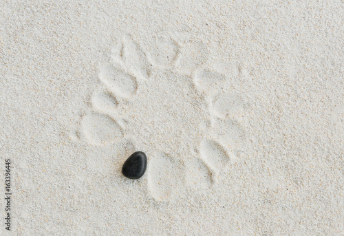 black stone on white sand background with stone footprint