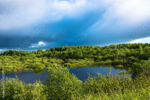 Landscape with a small lake and stormy skies.