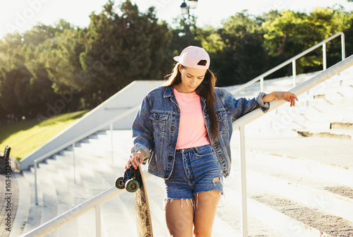 Young girl with longboard in the park at sunrise or sunset