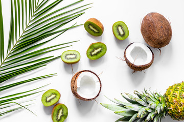 Summer exotic fruits. Kiwi, cocount, pineapple and palm branch on white background top view