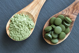 Chlorella and young barley powder on two wooden spoons - 163408845