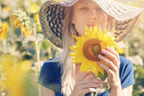 Summer Portrait of happy smiling woman holding sunflower outdoors.