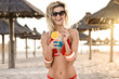 Gorgeous woman in red bikini drinks cocktail Blue lagoon on the beach