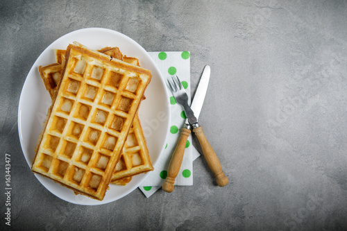 Freshly baked belgium waffles in plate with copy space. From top view