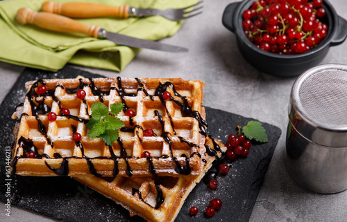 Plate of belgian waffles with chocolate sauce and currant fruit on dark gray background. From top view.