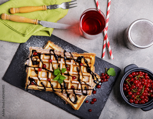 Plate of belgian waffles with chocolate sauce and currant fruit on dark gray background. From top view