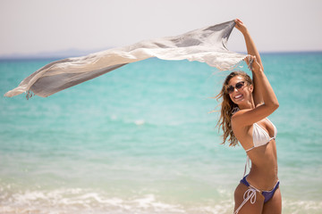 Beautiful young woman holding a scarf in the wind on the beach