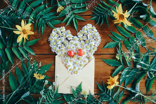 Envelope with chamomile flowers and green leaves on a wooden background