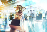 Man holding up a gold trophy cup,win concept. - 163464613